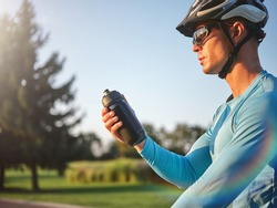 Hydration matters. Professional male cyclist holding water bottle, standing with his bike in park on a sunny day