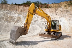 Hydraulic crawler excavator working in quarries. Yellow earthmoving machine packs gravel in a quarry.