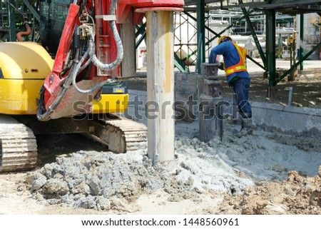 Hydraulic drilling machine is boring holes in the construction site for bored concrete piles work to be the foundation and workers are bringing sand from the drill head.