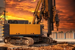 Hydraulic drilling rig against the backdrop of the sunset sky. Installation of bored piles by drilling. Foundations and foundations. Drilling in the ground