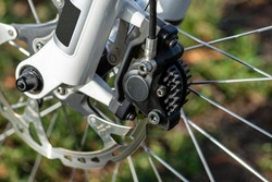 Hydraulic front disc brake on mountain bike with bicycle hub, caliper and spokes.