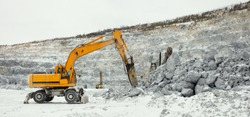 Hydraulic hammer and other mining machinery in a limestone quarry on a winter cloudy day, panorama.