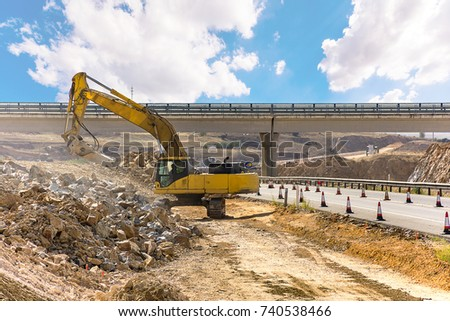 Hydraulic hammer working on the construction of a road