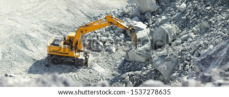 Hydraulic hammer works in a quarry against the background of huge gray stones, panorama.