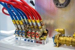 Hydraulic high pressure hoses and valves on mold control system of cooling with red and blue tubes - part of automatic injection molding machine