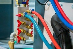 Hydraulic high pressure hoses and valves on mold control system of water cooling with red and blue tubes - part of automatic injection molding machine: close up view