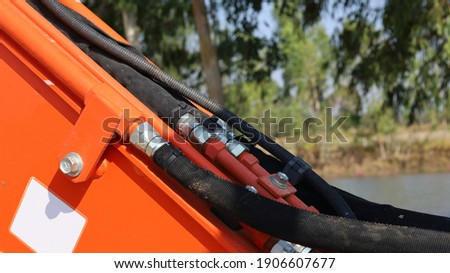 Hydraulic hose couplings are dirty. Metal hose attached to black rubber hose of heavy equipment pressurized oil transmission system with copy space. Focus closely and choose the subject.