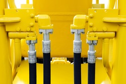 Hydraulic hoses and steel connectors for bulldozers, tractors, excavators and loaders, four, rubber tubes with screws and bolts of yellow machine, construction heavy industry detail