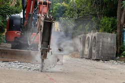 Hydraulic jackhammer from excavator construction truck drilling concrete ground with flying fragment concrete and dusty. Background for pm 2.5 micro dust problem and noise pollution or drainage system