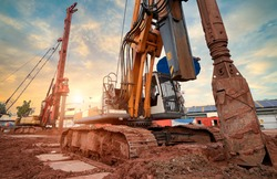 Hydraulic pile drilling machine worker digging at industrial construction site. Hydraulic Drilling Rig. Device of bored pile with casing. Foundation and ground. Drilling in the ground. Technologies.