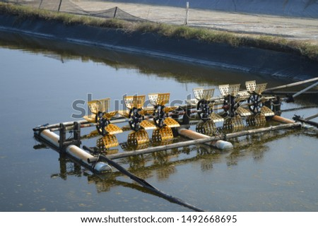 Hydraulic turbine water or the paddle wheel aerator active in aquaculture pond for improve water quality. #1492668695