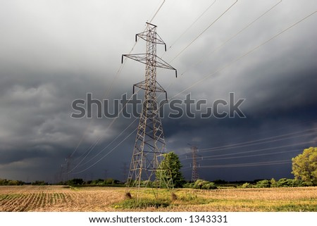 Hydro towers in a farm field with impending thunderstorm in background