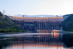 Hydroelectric arched structure, made of concrete in the evening with the lights reflecting in the river, after leaving the dam.