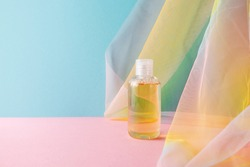 Hydrophilic cleanser oil on blue pink background with colorful rainbow organza fabric drapery. Makeup remover cosmetic beauty product mockup. Healthcare skincare concept