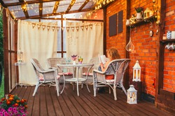Hygge balcony concept. Woman reading a paper book on home balcony outdoors. Party string lights illuminating the space. Lot of candles and lanterns, curtains hanging with rustic heart party flags.