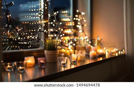 hygge, decoration and christmas concept - candles burning in lanterns on window sill and festive garland string at home