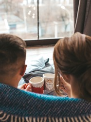 hygge, leisure and christmas concept - close up of couple drinking hot chocolate with marshmallow at home.