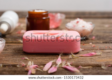 hygiene, beauty products, pink soap, cream, bath salt, tincture, old wooden table background