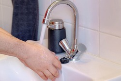 Hygiene concept, Selective focus of a man hand washing his hand in basin, Blurred sink and tab water as background, To prevent the Coronavirus disease (COVID-19) scourge is to wash hands frequently.