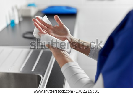 hygiene, health care and safety concept - close up of female doctor or nurse drying hands with paper tissue at hospital