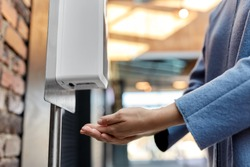 hygiene, health care and safety concept - close up of woman using hand sanitizer from dispenser at shopping mall
