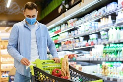 Hygiene, Healthcare And Prevention Concept. Man cleaning handle of shopping trolley cart, using antivirus antibacterial wet wipe napkin to protect himself from bacteria and virus, wearing face mask