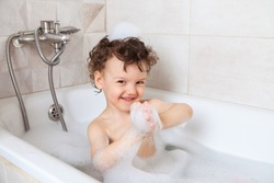 hygiene. the child bathes in a bath with foam. Occupation during coronavirus quarantine. Washing a child after a walk on the street. Disinfection and protection against dirt, germs and viruses