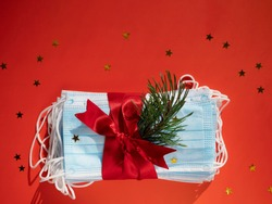 Hygienic face masks as a gift with a red ribbon, Christmas and New Year 2021 decor on a red background with space for text. Holidays self-isolation and coronavirus pandemic concept