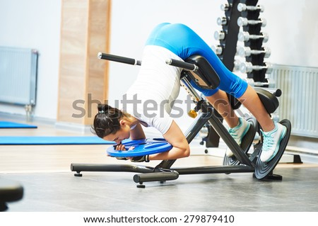 Hyperextension. fitness and sport concept. personal coach trainer woman work out at a gym with heavy weight