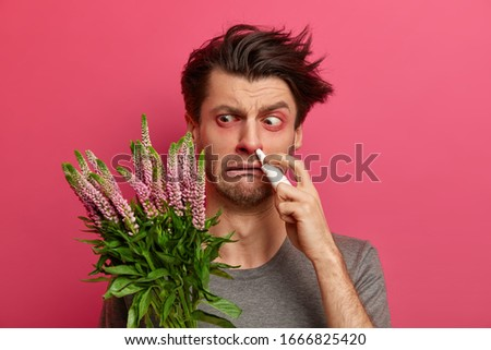 Hypersensitive man has hay fever, his immune system reacts to foreign substance, has swollen red eyes, uses nasal drops for effective treatment, stands indoor. Seasonal allergy and rhnitis concept Stock photo ©