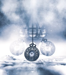 Hypnotising watch on a chain swinging above clouds. Time concept. Blue tones and vertical framing