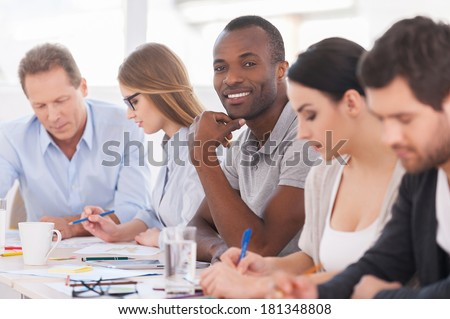 I am a part of strong and creative team. Group of business people sitting in a row at the table while handsome African man looking at camera and smiling #181348808