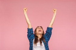 I am champion! Motivated enthusiastic girl in checkered shirt screaming for joy and raising high her fists, celebrating successful winning, incredible victory. studio shot isolated on pink background