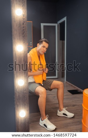 I am handsome. Serious handsome man looking at his reflection while sitting in the changing room #1468597724