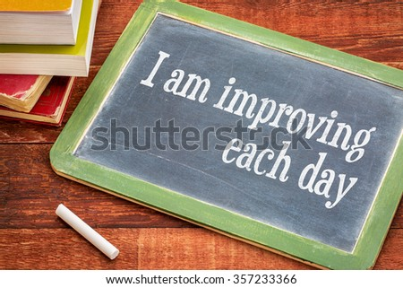I am improving each day - self development concept or positive affirmation on a  slate blackboard with a white chalk and a stack of books against rustic wooden table