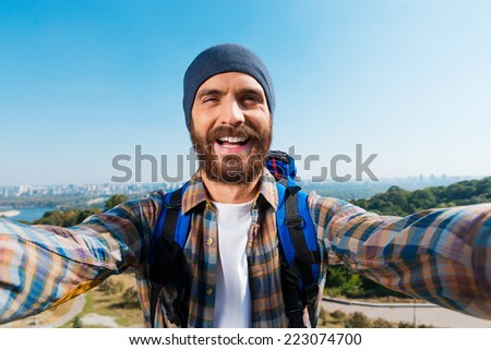 I am in the most beautiful place! Handsome young man carrying backpack and taking a picture of himself