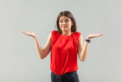 I am not sure! Portrait of confused beautiful brunette young woman in red shirt standing with raised arms, looking away and do'nt know what to do. indoor, studio shot, isolated on gray background.