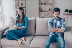 I am not talking to you! Mistrust and cheat problems. Annoyed couple is ignoring each other, sitting on the couch indoors at home with sad faces