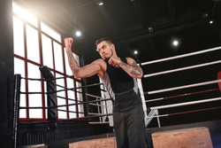 I am ready to fight Strong athlete in sports clothing boxing with shadow opposite boxing ring. Muscular man practicing an uppercut