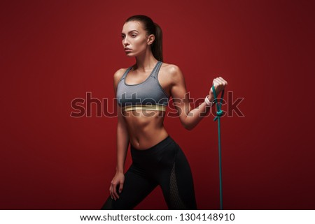 I am training to become the best. Beautiful sportswoman performs exercises with resistance band over red background