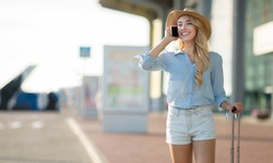 I Arrived. Young woman traveller wearing sun hat, talking on mobile phone after flight arrival in airport, free space