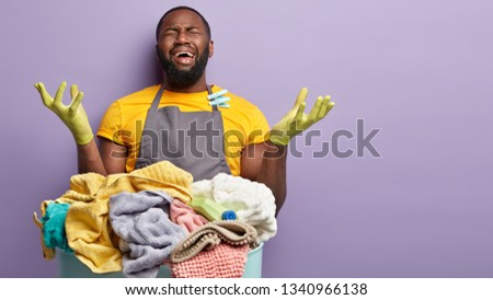 I bless you, give me rest. Stressful emotive black man cries from negative emotions, raises hands in frustration, being in panic as works hard without rest, has much household duties. Housekeeping #1340966138