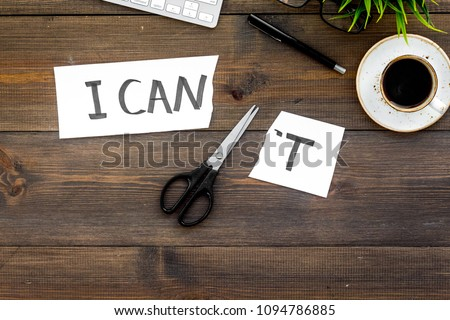 I can concept. Encourage youself. Scissors cut off the letter t of written word I can't. Office desk. Dark wooden background top view space for text