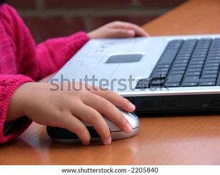 I can do it ! -- Close-up image of a little girl learning how to use computer to surf the Internet.