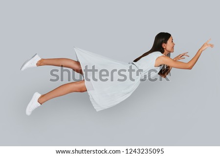 I can fly! Beautiful young Asian woman smiling while hovering in air against grey background