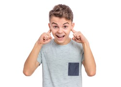 I can not hear anything - portrait of young caucasian teen boy covering ears. Funny teenager 15 year old. Child isolated on white background. Boy closing ears with fingers. Hear no evil concept.