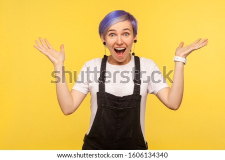I can't believe this! Portrait of amazed hipster girl with violet short hair in denim overalls raising hands from sudden surprise, awesome shocking news. isolated on yellow background, studio shot