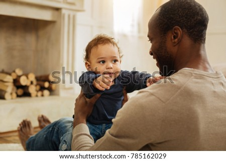 I cherish you. Cheerful dark-haired bearded afro-american man smiling and playing with his happy young son while sitting on the floor