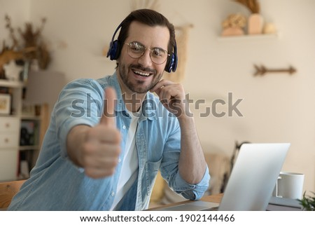 I choose. Portrait of smiling young businessman in wireless earphones distracted from conference webinar on pc screen. Millennial man student looking at camera hold thumb up recommend remote learning Foto d'archivio ©