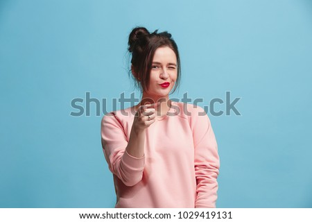 Photo of  I choose you and order. The smiling business woman point you, want you, half length closeup portrait on blue studio background. The human emotions, facial expression concept. Front view. Trendy colors